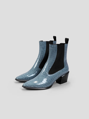 "3/4 front view: This ankle-high sleek Chelsea boot is crafted from a dusty blue croc-embossed patent cow leather. Light western influences including a squared toe and Cuban heels measuring 2.25"". Contrasting black, elastic side panels and back pull tabs for easy pull on and off. Padded footbed. Certified organic cotton lining."