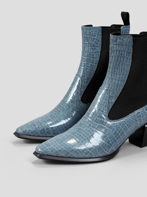 "Side view: This ankle-high sleek Chelsea boot is crafted from a dusty blue croc-embossed patent cow leather. Light western influences including a squared toe and Cuban heels measuring 2.25"". Contrasting black, elastic side panels and back pull tabs for easy pull on and off. Padded footbed. Certified organic cotton lining."