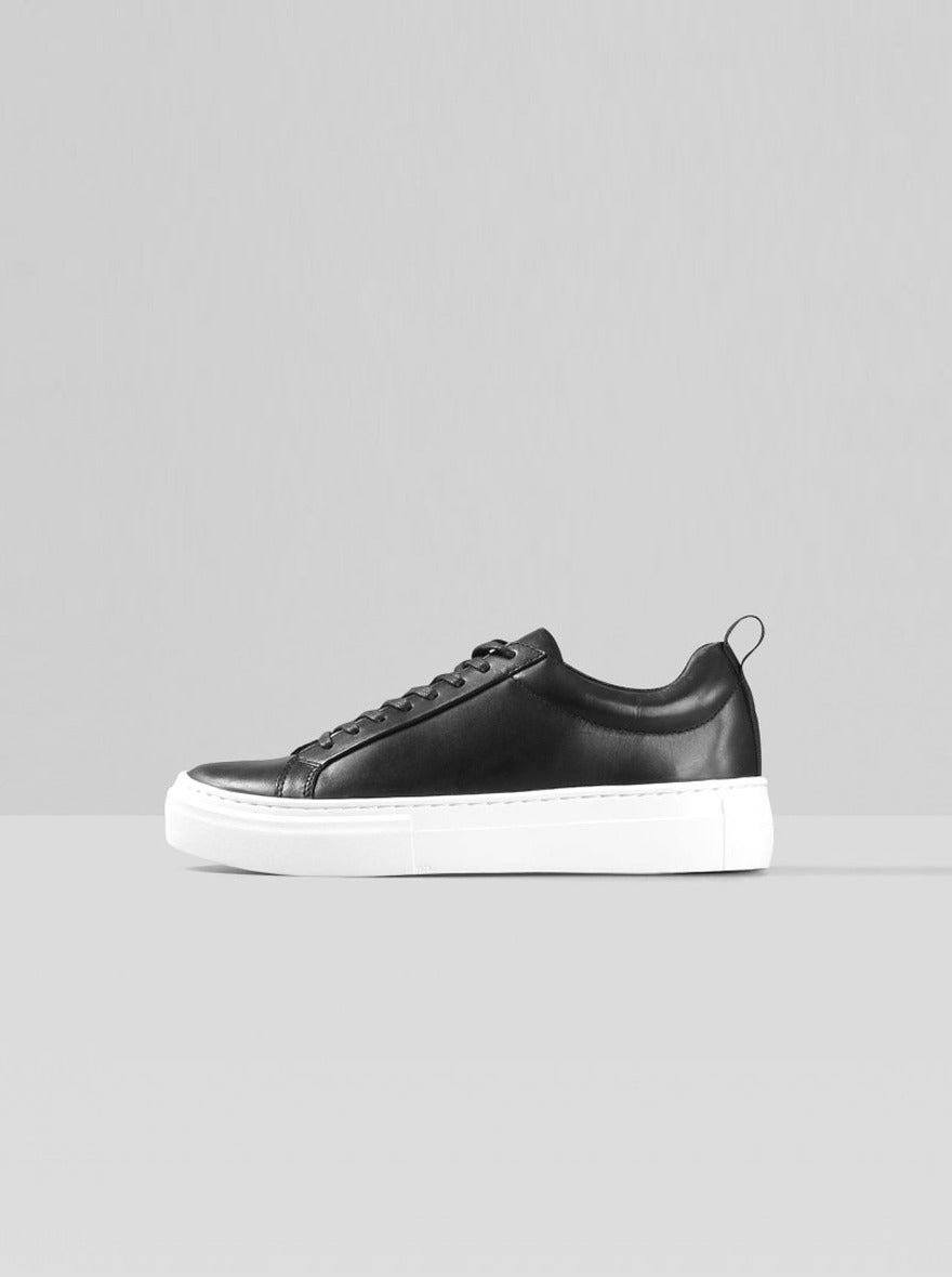 "Side view: This classic style laced sneaker is elevated with a chunky rubber sole for height and comfort, measuring 1.5"". The minimalistic upper is crafted from smooth black cow leather, 100% recycled polyester lining and waxed cotton laces. The insole is made from chrome-free tanned leather. Padded back collar and heel loop tab at the back."