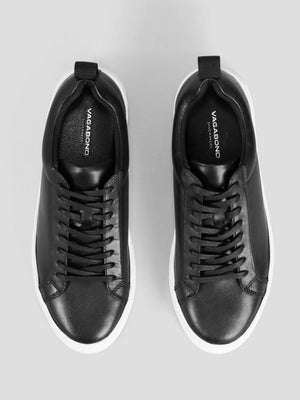 "Top view: This classic style laced sneaker is elevated with a chunky rubber sole for height and comfort, measuring 1.5"". The minimalistic upper is crafted from smooth black cow leather, 100% recycled polyester lining and waxed cotton laces. The insole is made from chrome-free tanned leather. Padded back collar and heel loop tab at the back."