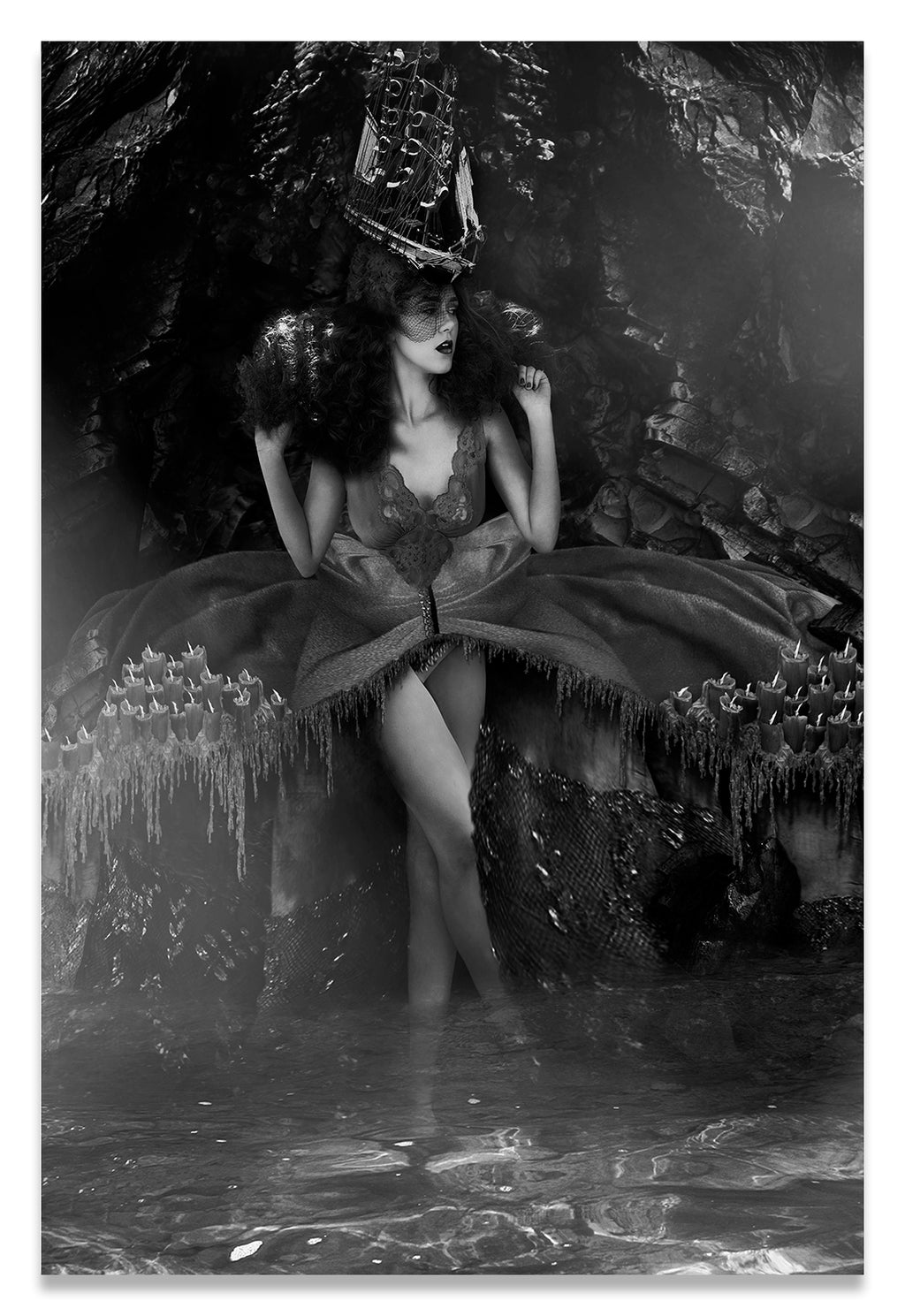 Vertical Black and White Portrait of a Woman Standing in Water in Purgatory; adorned with a Ship Hat and Melted Candles Along Her Dress.