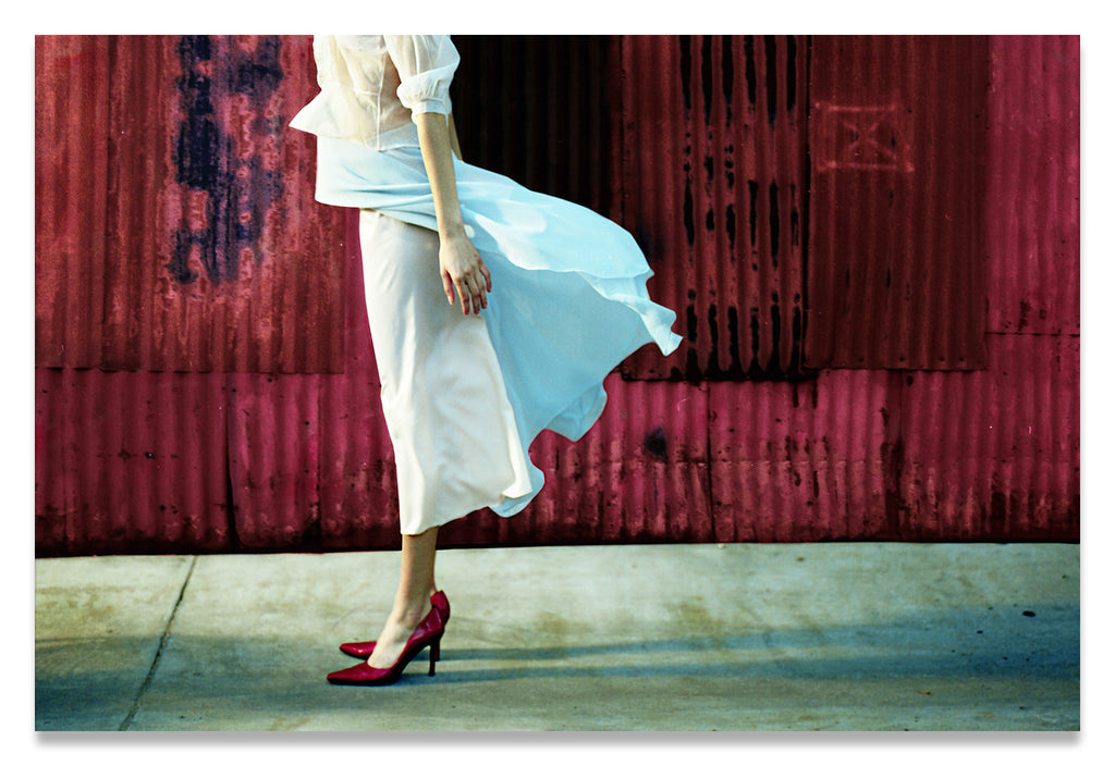 Profile of  a Headless Woman in Crimson Red Shoes, against a Crimson Red Metal Wall.