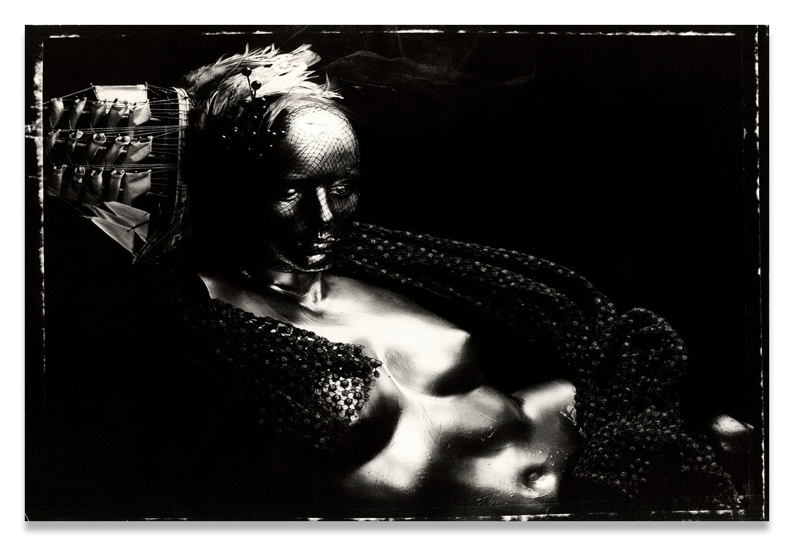 Horizontal Black and White Portrait, on Polaroid 55, of a nude, metallic mannequin torso with a Ship Hat and Feather Headpiece along the side of the Head- Fine Art Print