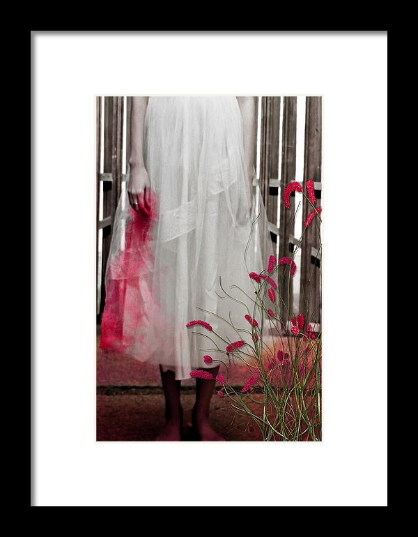 Woman in a Vintage White Lace Dress, cropped at waist, Standing With a Bloody Hand Dripping Down Her Dress in front of a Gate-Framed Print