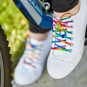 tie dye shoelaces on white chucks on a bike pedal