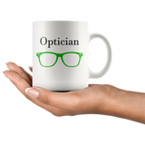 """Optician"" and green glasses on white mug in hand"