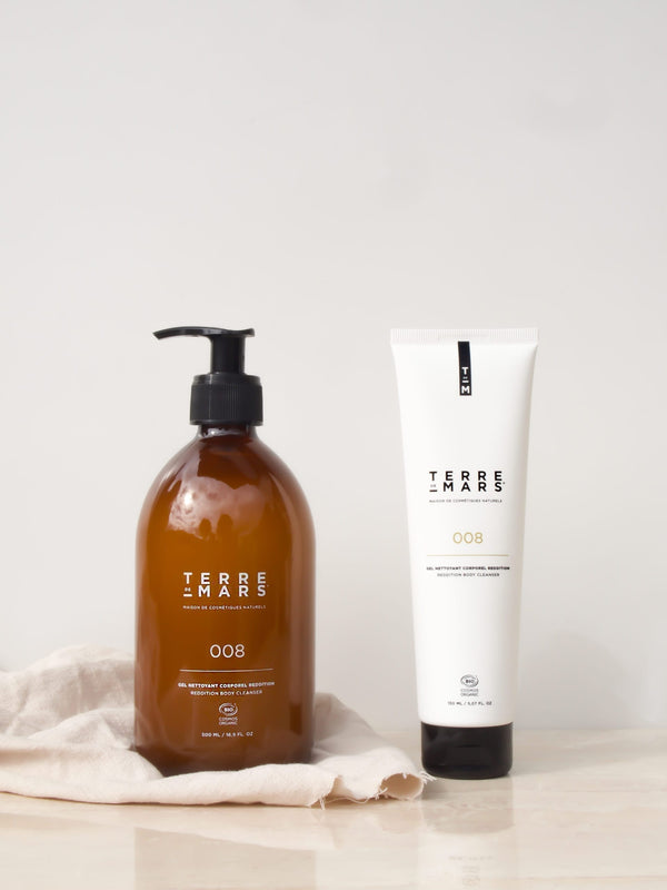 Amber glass 500ml bottle and 150ml white plastic bottle of reddition body cleanser by French brand Terre de Mars