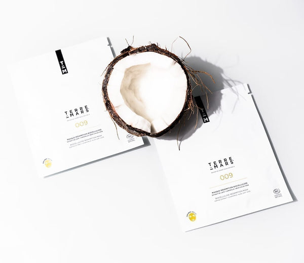 white package of terre de mars 009 redemption biocellulose biodegradable sheet mask and half a coconut