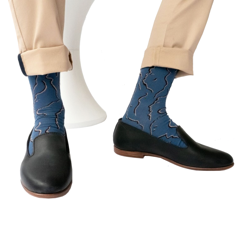 Close up of cool socks designed by French brand Bonne Maison featuring the face profiles on denim background