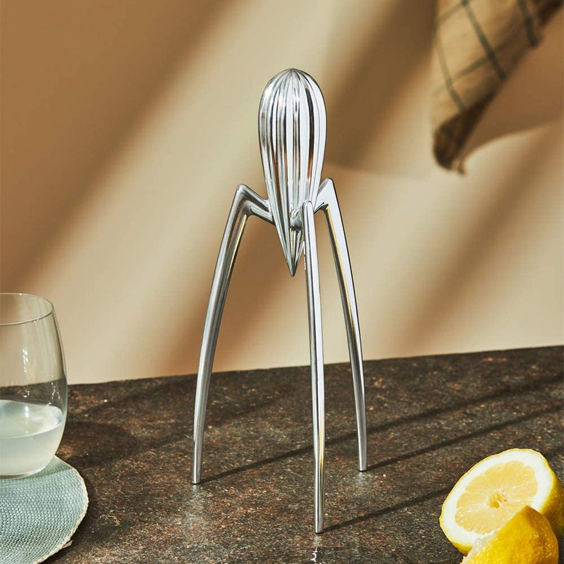 Alessi Juicy Salif citrus juicer in aluminium casting in a kitchen counter with a lemon cut in half and a glass with lemon juice