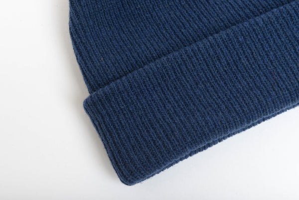 Close up of natural merino wool beanie hat in dark blue
