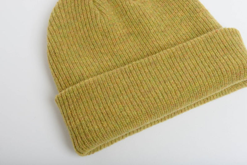 close up details of natural merino wool beanie hat in mustard