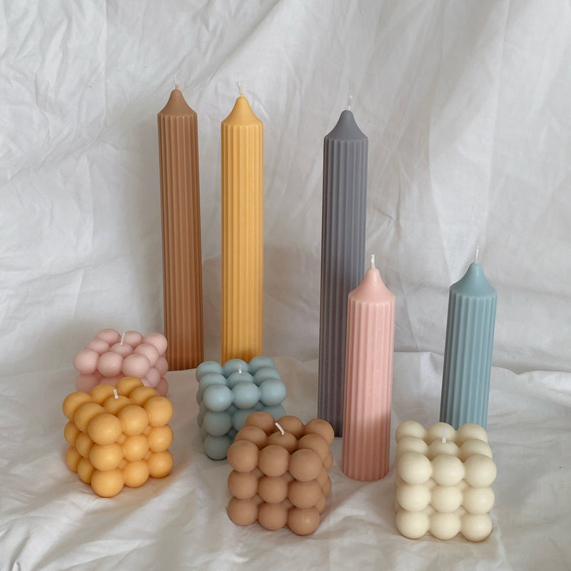 bunch of pastel coloured pillar candles on white sheet