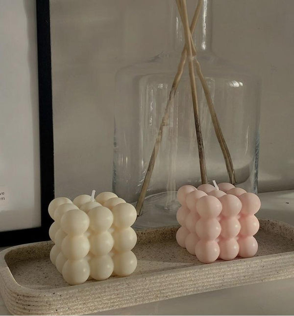 cream and pale pink bubble soy candles in cube shape on a ceramic tray with a dried flower bunch behind in a wide glass vase
