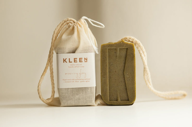 Picture with two Tea Tree oil exfoliating soaps on a cotton rope by natural skincare brand Kleen soaps ideal for oily skin and a cotton travel bag