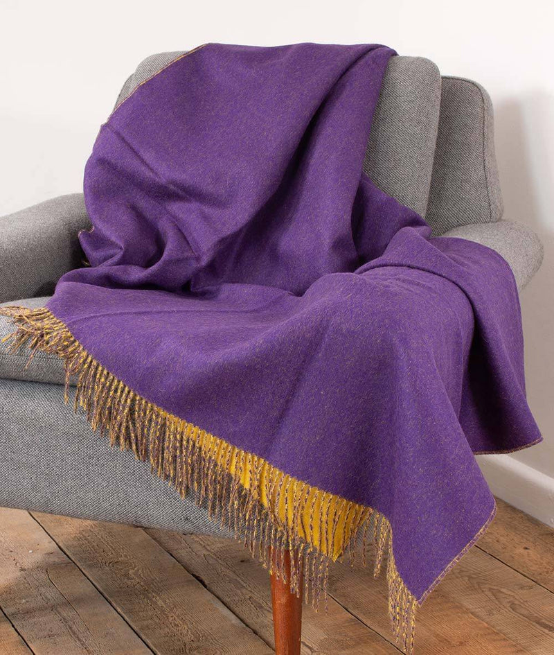 Lifestyle picture of Woven purple and yellow reversible Baby Alpaca soft blanket designed in the UK by So Cosy