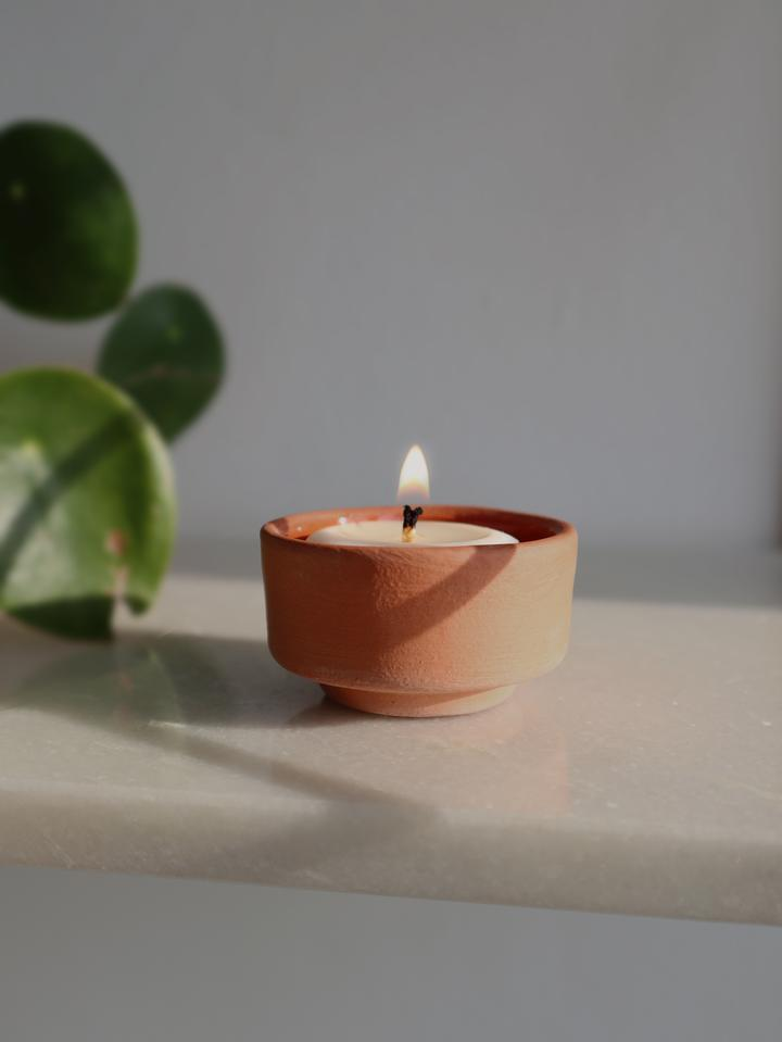close up naeba handmade rapeseed vegan tealight candles with essential oils in a terracotta holder