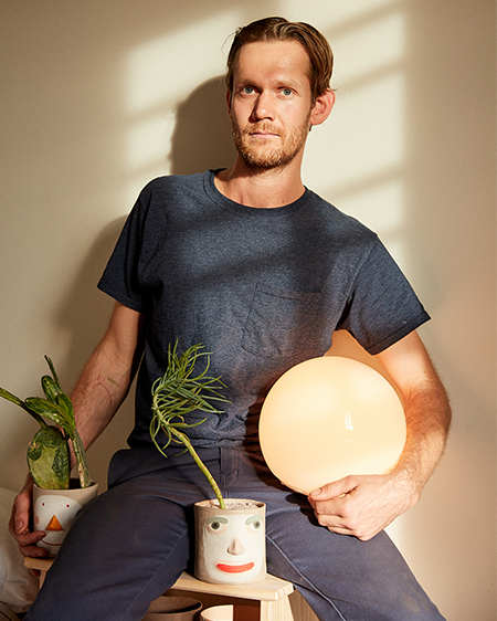 Founder of ceramics brand Group Partner holding one of his handmade planters