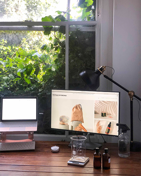 Palm of Feronia home studio with two laptops, essential oils and beaker