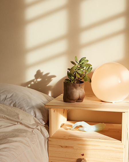 Bedroom during sunset with a ceramic nude planter and a lamp on top of a wooden bedside table