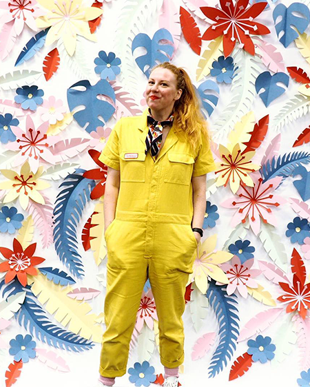 Wall decorated with paper plants and flowers in blues, yellows, reds and pinks with illustrator Jacqueline Colley in a bright yellow jumpsuit