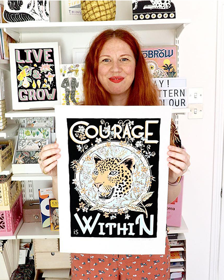Illustrator Jacqueline Colley holding her A3 Courage Within Screen Print that showcases a leopard with a background of wild flowers in pastel colours