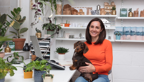 Another Studio Founder Aimee at her studio full of plants, pots and her pup