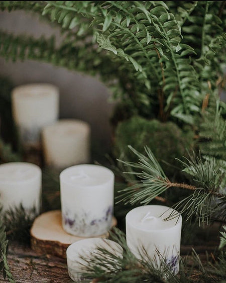 Selection of soy wax candles with herbs and grass