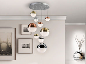 Many sphere shaped ceiling lamps all varying in size hanging from a silver chrome base in living room.