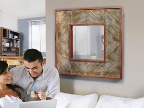 Medium sized wood and copper square mirror, mounted on wall next to couple.