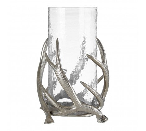 Glass candle holder held within metal antlers on a white background.
