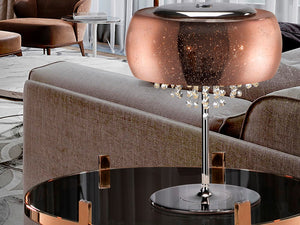 Copper coloured lamp with a chrome finish placed on a table-side next to a sofa.