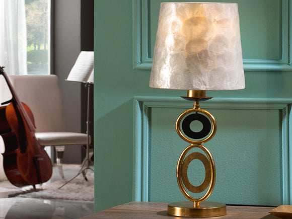 Golden, delicate circular style table lamp, placed on a living room table.