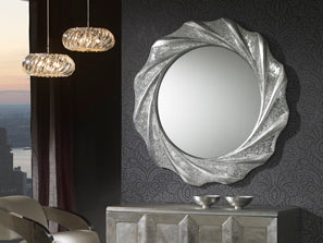 Large circular mirror, strong looking with a chrome finish placed above a table.