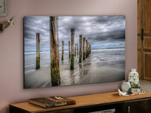 Large rectangular artwork of the sea, several wooden pillars line the horizon.