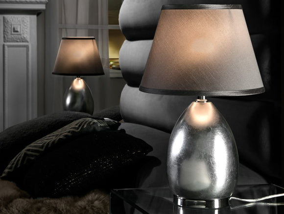 Medium sized, simple bedside table lamp, smooth chrome oval base with a lamp shade above.