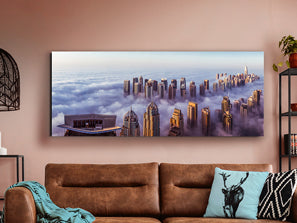 Large rectangular artwork of a city skyline above the clouds.