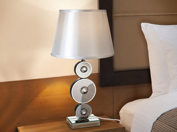 Medium sized bedside table lamp with stacked mirrored circles used as a pole to hold up the lampshade.