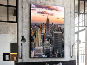 Large portrait artwork of New York skyline with the empire state building at its centre, behind is a sunset.
