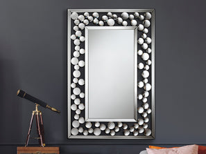 Medium to large sized mirror, bordered with white decorative spheres hanging on wall.