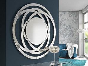 Large circular mirror resembling a flower, placed on a black wall in living room.