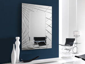 Very large portrait mirror placed on a dark blue wall. Mirror bordered with silver streaks.