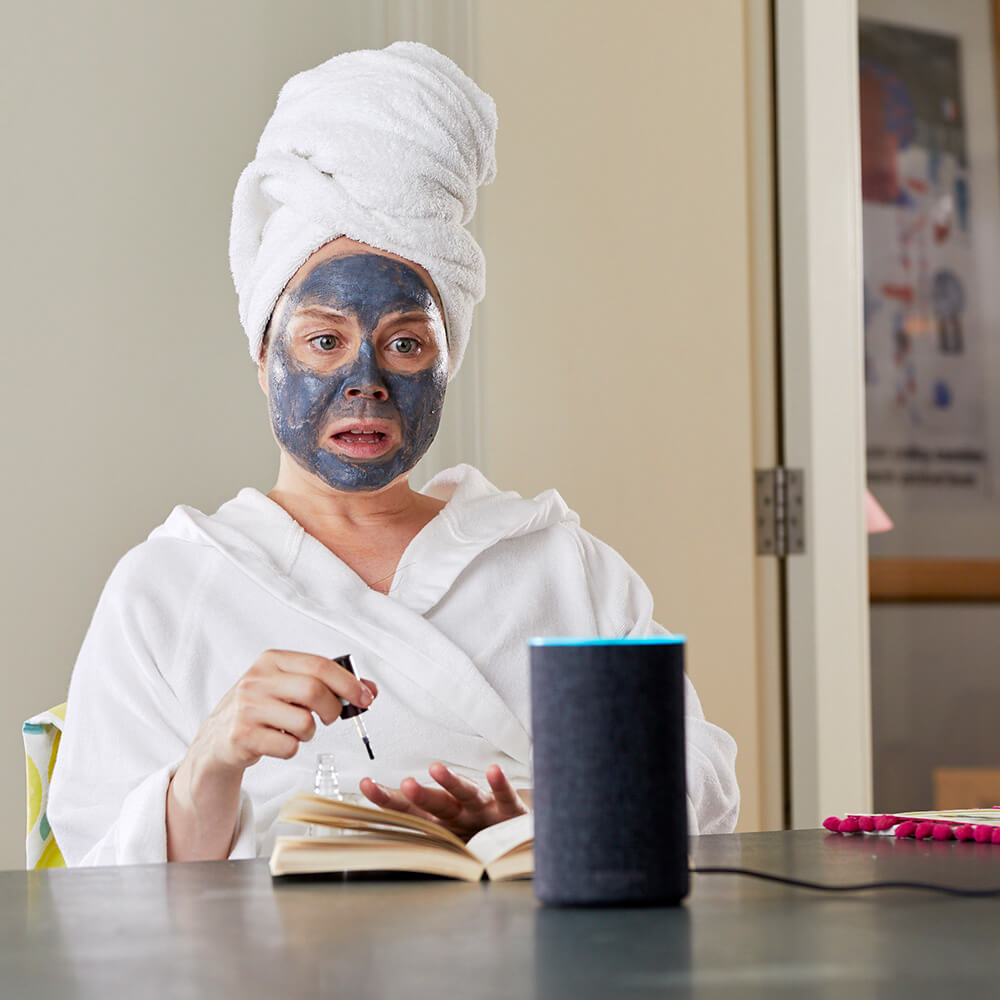 Woman wearing face mask surprised expression at Amazon Echo