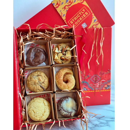 a red cookie box filled with 6 different types of soft and round cookies