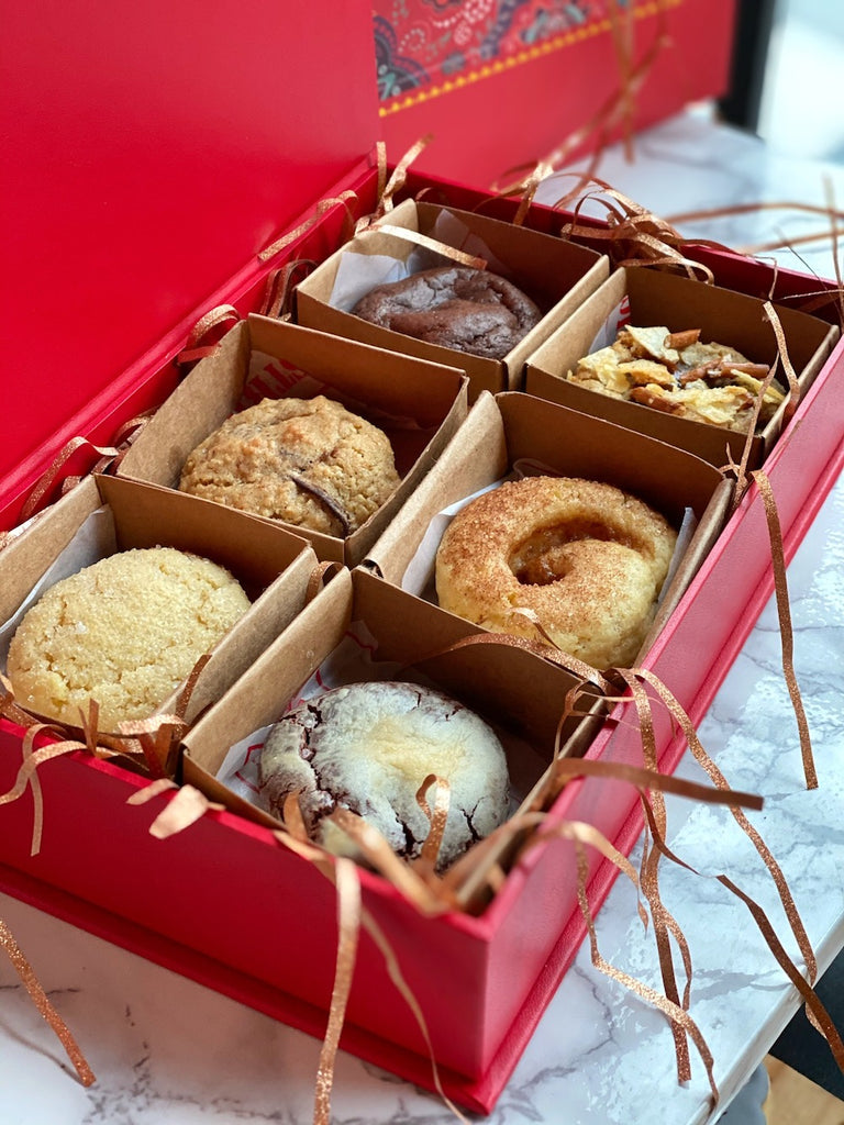 a red gift box of cookies with 6 different flavors inside