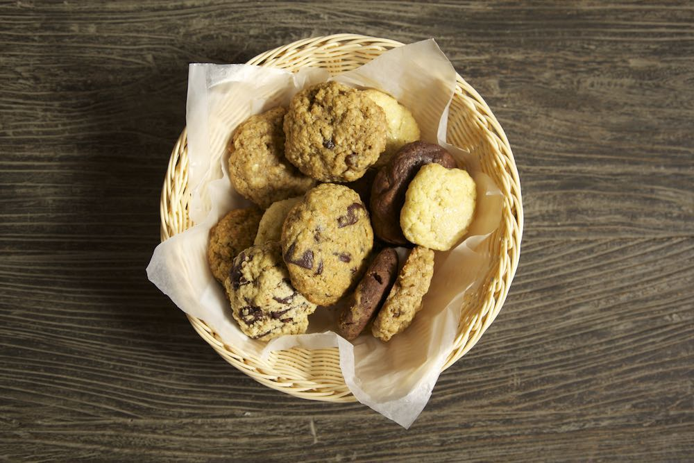 a basket of soft cookies on top of a wooden table