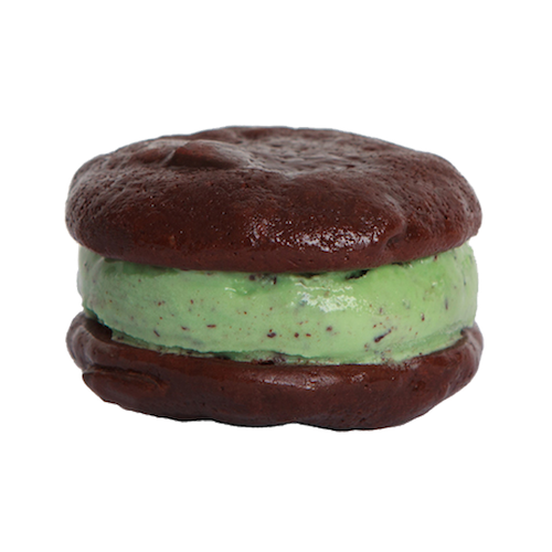 an ice cream sandwich that has two brownie cookies sandwiching mint chocolate chip ice cream
