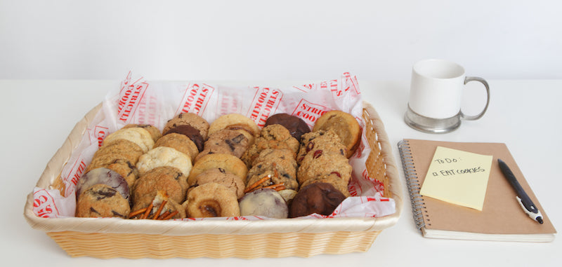 a basket of many cookies on a desk with a coffee cup