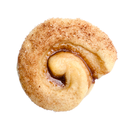 a round sugar cookie with a coating of cinnamon and sugar with a swirl of cinnamon goo in the middle
