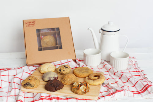 cookie box with a mix of cookies on a cutting board with 2 mugs and a pot of coffee